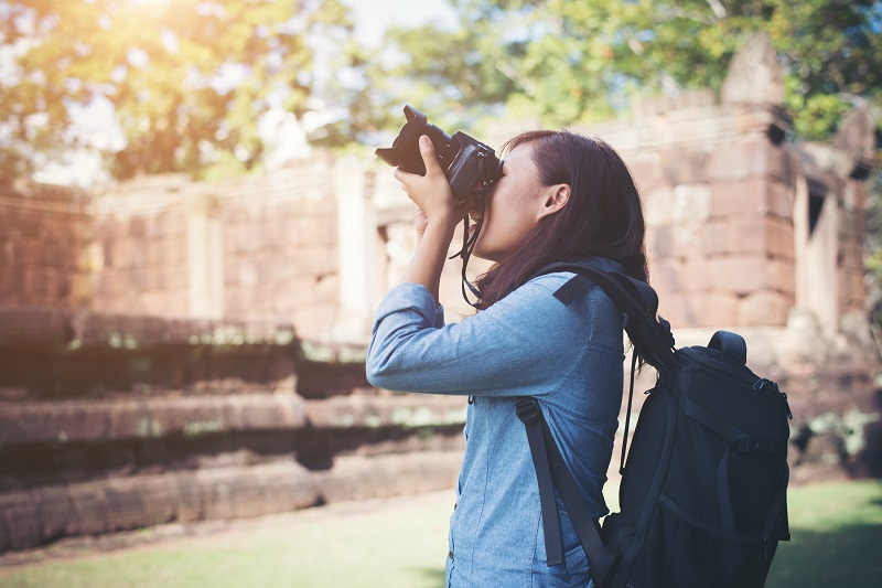 Young attractive woman photographer tourist with backpack coming